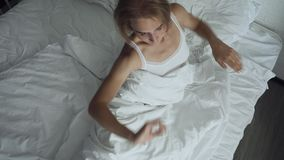 Woman awakening in comfortable cozy bed stretching and gets up. Young woman awakening in comfortable cozy bed stretching and gets up. Top view stock footage