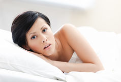 Woman awakes in the bed. White background Stock Photography