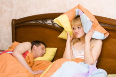 Woman awaking by her husband snoring. Male snoring on the bed and her wife can not sleep. Couple in bed with woman trying to sleep with man snoring. A young lady Royalty Free Stock Photography