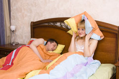 Woman awaking by her husband snoring. Male snoring on the bed and her wife can not sleep. Couple in bed with woman trying to sleep with man snoring. A young Royalty Free Stock Photo