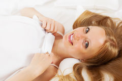 Woman awaking up on white sheet in bed Stock Images