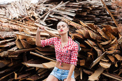 Woman ax in hand in a plaid shirt Stock Images
