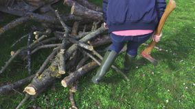 Woman with ax near firewood. In summer day stock footage