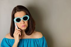 Woman in azure dress and sunglasses talking on a smartphone. Selective focus Royalty Free Stock Photos