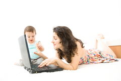 Babysitting. Woman babysitter and baby fighting over laptop Royalty Free Stock Photography