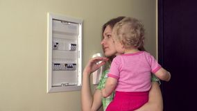 Woman with baby in arm check circuit breaker electrical home. 4K. Woman housewife with little baby girl in arms check the circuit  breaker electrical in own home stock footage
