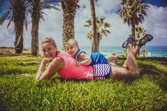 Woman with baby boy in grass at seaside