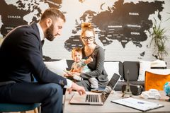 Woman and baby boy with travel agent at the office. Happy family sitting with men agent at the travel agency office with beautiful map on the background choosing Stock Photography