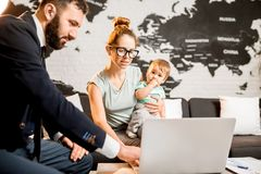 Woman and baby boy with travel agent at the office. Happy family sitting with men agent at the travel agency office with beautiful map on the background choosing Royalty Free Stock Photography