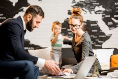 Woman and baby boy with travel agent at the office. Happy family sitting with men agent at the travel agency office with beautiful map on the background choosing Royalty Free Stock Image