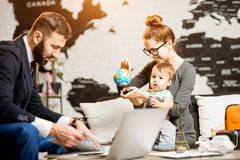 Woman and baby boy with travel agent at the office. Happy family sitting with men agent at the travel agency office with beautiful map on the background playing Royalty Free Stock Images