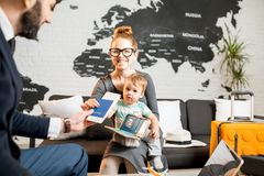Woman and baby boy with travel agent at the office. Happy family sitting with men agent at the travel agency office with beautiful map on the background Stock Photo