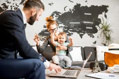 Woman and baby boy with travel agent at the office. Happy family sitting with men agent at the travel agency office with beautiful map on the background choosing Royalty Free Stock Photo