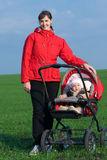 Woman with baby buggy Royalty Free Stock Photography