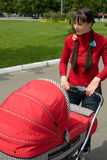 Woman with baby carriage. Young woman with red baby carriage Royalty Free Stock Photos
