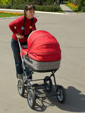 Woman with baby carriage. Young woman with red baby carriage Royalty Free Stock Photo