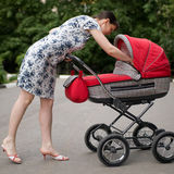 Woman with baby carriage. Young woman with red baby carriage Stock Photography