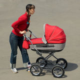 Woman with baby carriage. Young woman with red baby carriage Royalty Free Stock Images