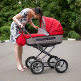 Woman with baby carriage. Young woman with red baby carriage Stock Photo