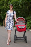 Woman with baby carriage. Young woman with red baby carriage Stock Image