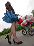 Woman with baby carriage. Young woman with red baby carriage Stock Images