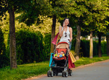 Woman With Baby Carriage Using Cell Phone In Park Royalty Free Stock Image