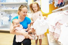 Woman with baby and child in clothes shop Stock Images