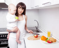 Woman with baby cooking Stock Image