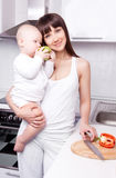 Woman with baby cooking Royalty Free Stock Image