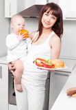 Woman with baby cooking Stock Photo