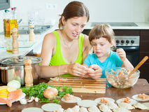 Woman with baby cooking fish dumplings (pelmeni) together Royalty Free Stock Photography