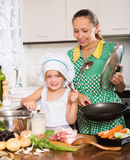 Woman with baby cooking at home Royalty Free Stock Photo