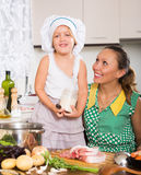 Woman with baby cooking at kitchen Stock Image