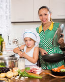 Woman with baby cooking at kitchen Stock Photos