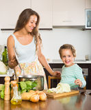 Woman with baby cooking at kitchen Royalty Free Stock Photos