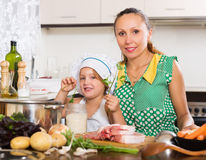 Woman with baby cooking at kitchen Stock Images