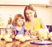 Woman with baby cooking with meat and vegetables Stock Photo