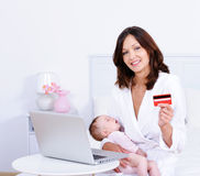 Woman with baby, credit card and laptop at home royalty free stock images