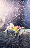 Woman in baby doll stile lying on a stone in the sun with teddy bear in hand Royalty Free Stock Image