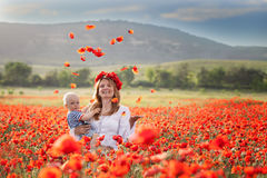 Woman with baby in a field of red poppies Stock Photography