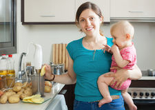 Woman with baby girl cooking mashed potatoes royalty free stock photo