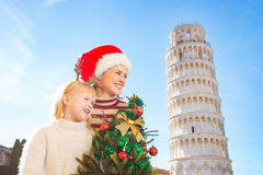 Woman and baby girl holding Christmas tree. Pisa, Italy Stock Images
