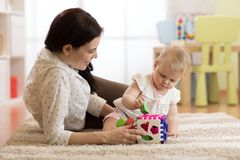 Mother and baby girl playing with developmental toys in nursery room stock image
