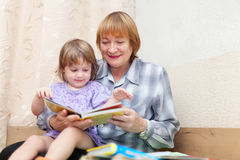 Woman and baby girl reads book Stock Image