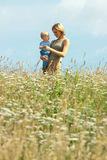 Woman with baby on her shoulders in a country Stock Images