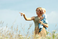 Woman with baby on her shoulders in a country Stock Image