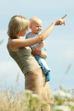 Woman with baby on her shoulders in a country Royalty Free Stock Images
