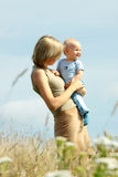 Woman with baby on her shoulders in a country Royalty Free Stock Image