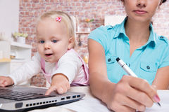 Woman with baby in the kitchen working with laptop Stock Photo