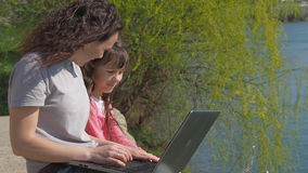 Woman with baby and laptop outdoors. Happy family on the river bank. Mother is teaching a child on a laptop. A spring sunny day. stock video